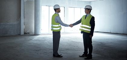 Two men at an empty construction site, in hard hats and hi-viz jackets, shaking hands
